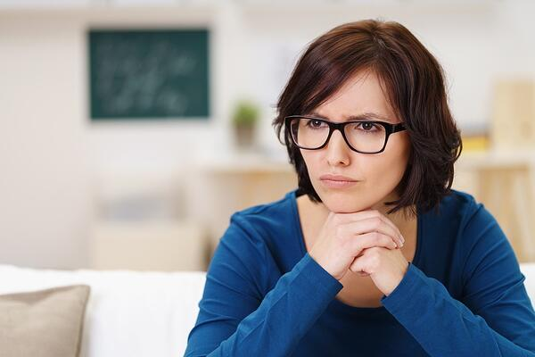 Pensive Woman Wearing Eyeglasses, Sitting on Couch at the Living Room and Looking Away with Chin Resting on her Hands..jpeg